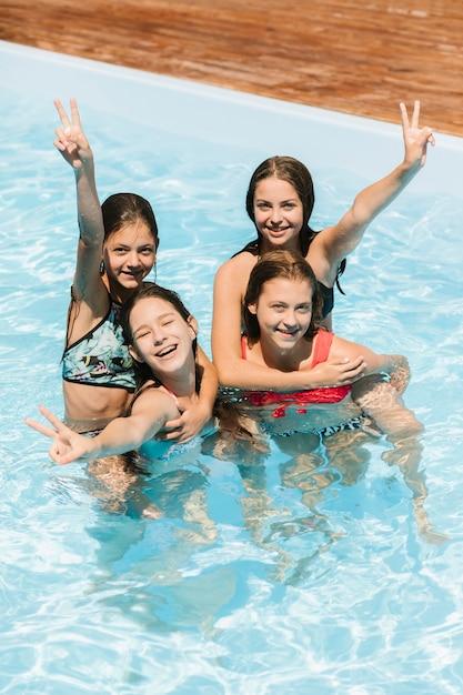 スイミングプールでピースサインを持って幸せな子供 無料写真