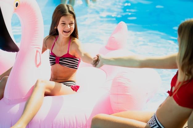 スイミングプールで手を取り合って幸せな子供 無料写真