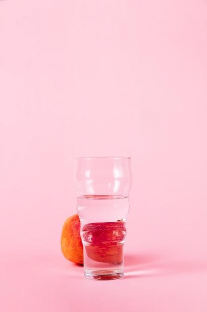 水とピンクの背景にネクタリンのガラス 無料写真