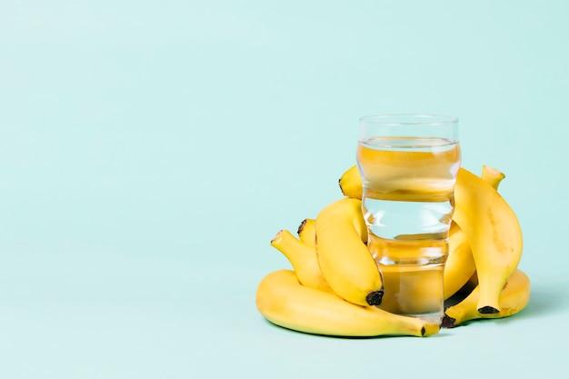 水のガラスの後ろにバナナの束 無料写真