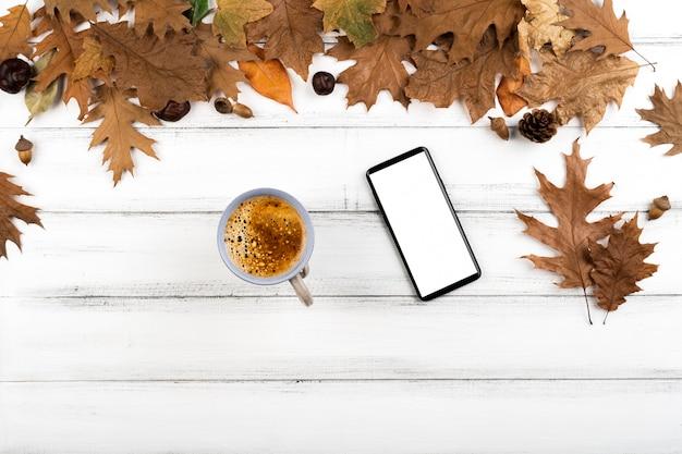 Макет кофе и смартфон на фоне листьев Бесплатные Фотографии