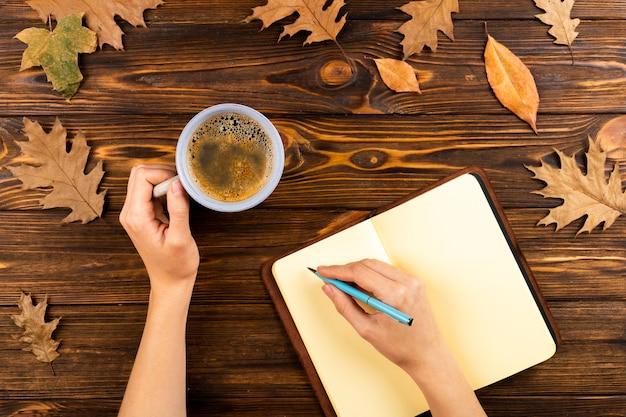 Кофе и блокнот на фоне осенних листьев Бесплатные Фотографии