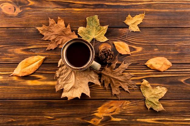 コーヒーと木製の背景の葉 無料写真