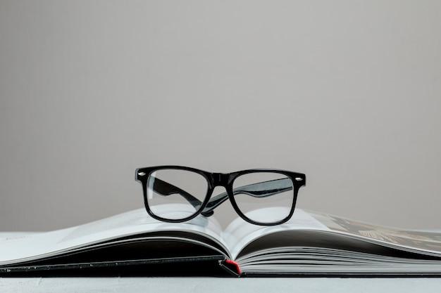 Вид спереди открытая книга в очках Бесплатные Фотографии