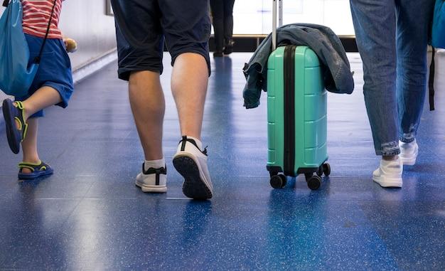 スーツケースで歩く人の背面図 無料写真