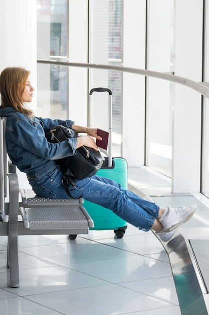 Вид сбоку женщины, сидящей в аэропорту Бесплатные Фотографии