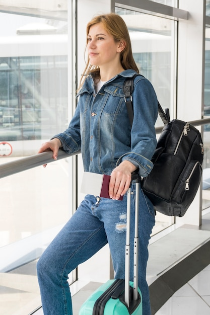 Средний снимок женщины, ожидающей ее полета Бесплатные Фотографии