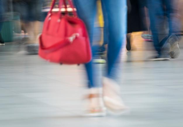 Размытые выстрел женщины с красной сумкой Бесплатные Фотографии