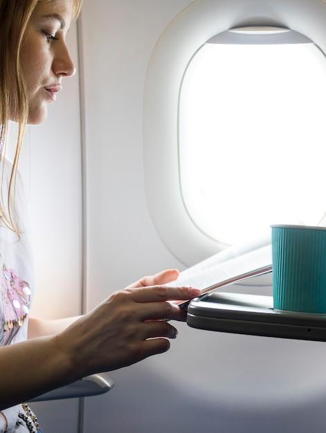飛行機のメニューを探している女性 無料写真