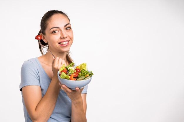 笑顔とサラダコピースペースを保持している女性 無料写真