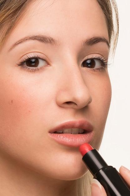 クローズアップ口紅を置く美しい女性 無料写真