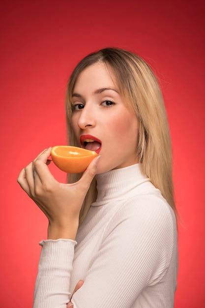 オレンジをかむ美しい女性 無料写真