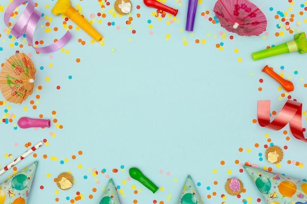 青の背景にパーティーの飾りとフラットレイアウトフレーム 無料写真