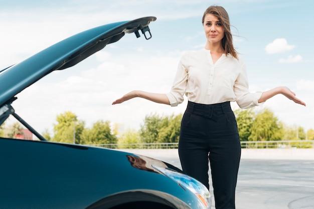 女性と車のミディアムショット 無料写真