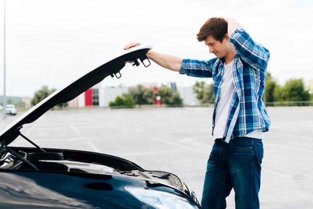 エンジンをチェックする男の側面図 無料写真