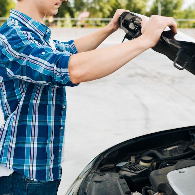 車のボンネットを開く男の側面図 無料写真