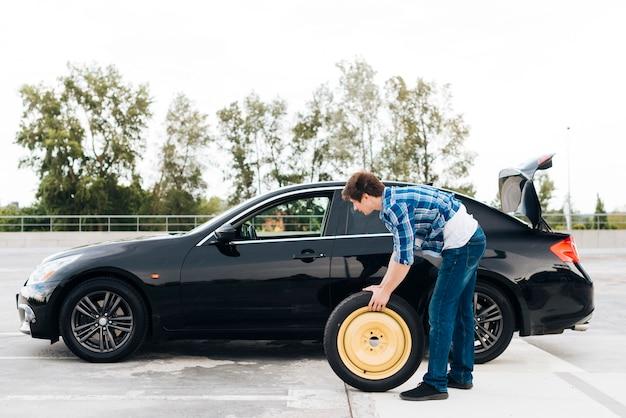 タイヤを交換する男のロングショット 無料写真