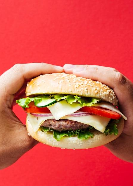 タマネギと赤の背景にチーズのハンバーガー 無料写真
