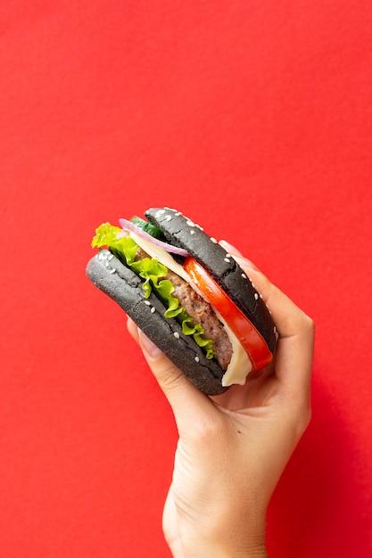 赤の背景に黒パンとハンバーガー 無料写真