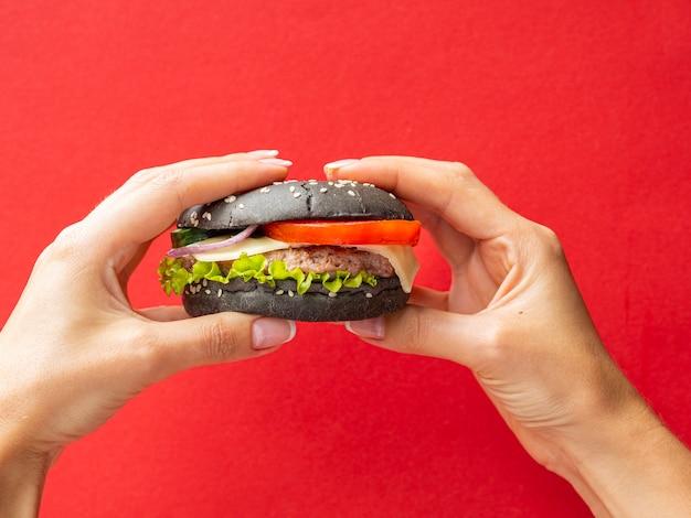 赤の背景にハンバーガーを保持手 無料写真