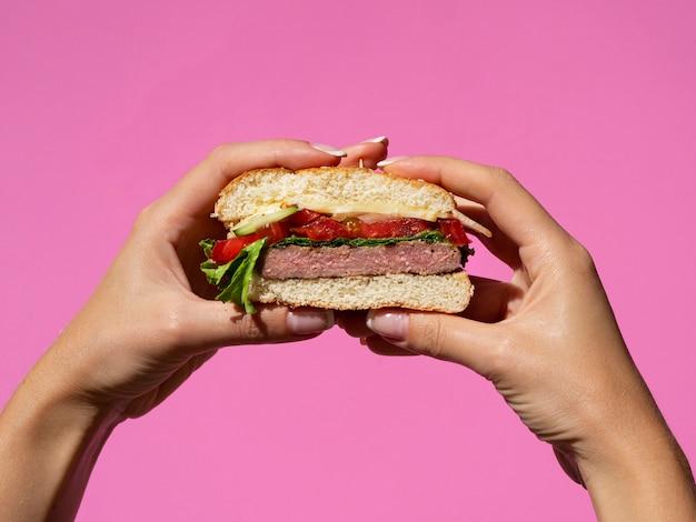 アメリカのおいしいハンバーガーを保持手 無料写真
