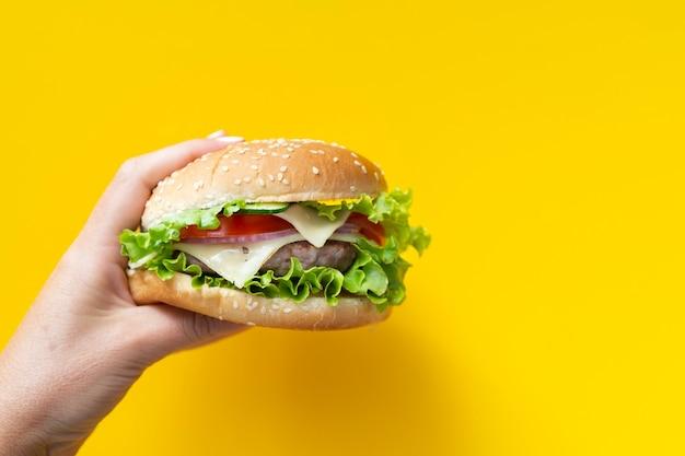黄色の背景の前にハンバーガー 無料写真