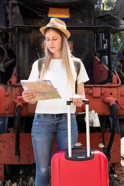 地図を見て彼女の荷物を持つ女性 無料写真