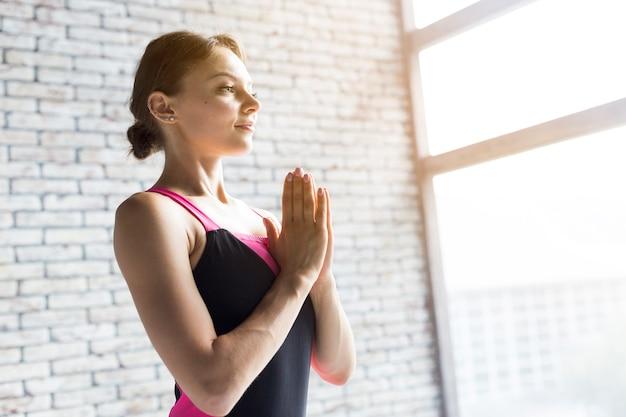 Женщина дышит, держа руки против ее груди Бесплатные Фотографии