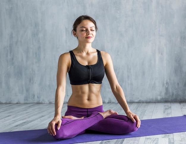Подходящая женщина, стоящая в позе лотоса во время медитации Бесплатные Фотографии
