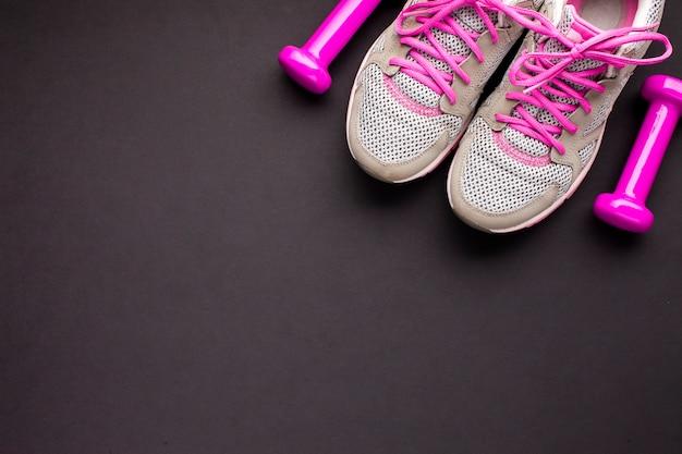 Композиция сверху с розовыми туфлями и гантелями Бесплатные Фотографии