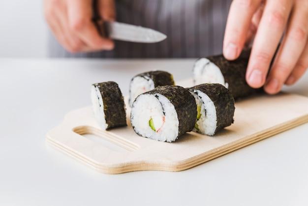 寿司のラップをカットボードにスライスする人 無料写真