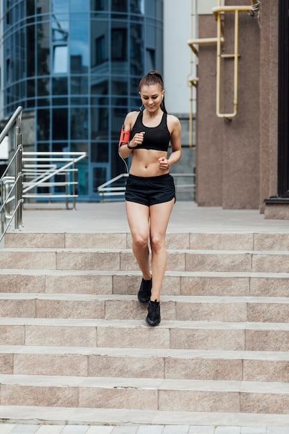 階段でジョギングの女性の正面図 無料写真