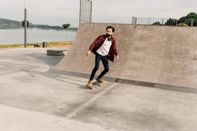スケートパークでの男のロングショット 無料写真