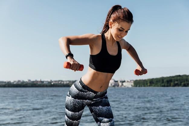 ウエイトトレーニングをしている女性の正面図 無料写真
