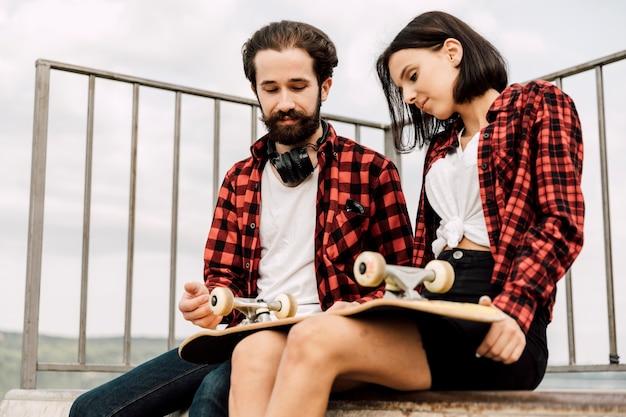 スケートパークでのカップルのミディアムショット 無料写真