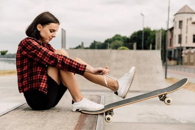 Вид сбоку женщины, связывая ее шнурки Бесплатные Фотографии
