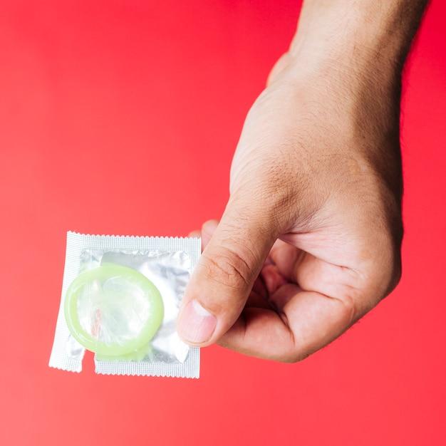 Рука крупным планом держит презерватив с красным фоном Бесплатные Фотографии