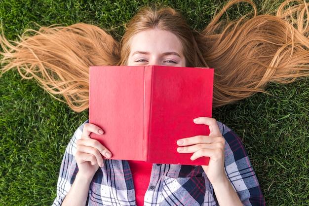 Вид сверху девушка закрыла рот книгой Бесплатные Фотографии