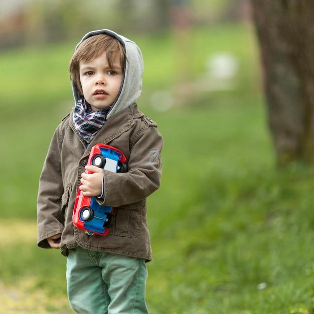Милый маленький мальчик держит игрушечную машинку Бесплатные Фотографии