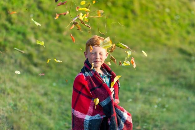 Рыжий мальчик играет с листьями Бесплатные Фотографии