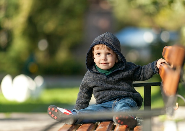 ベンチに手を握ってスマイリー少年 無料写真