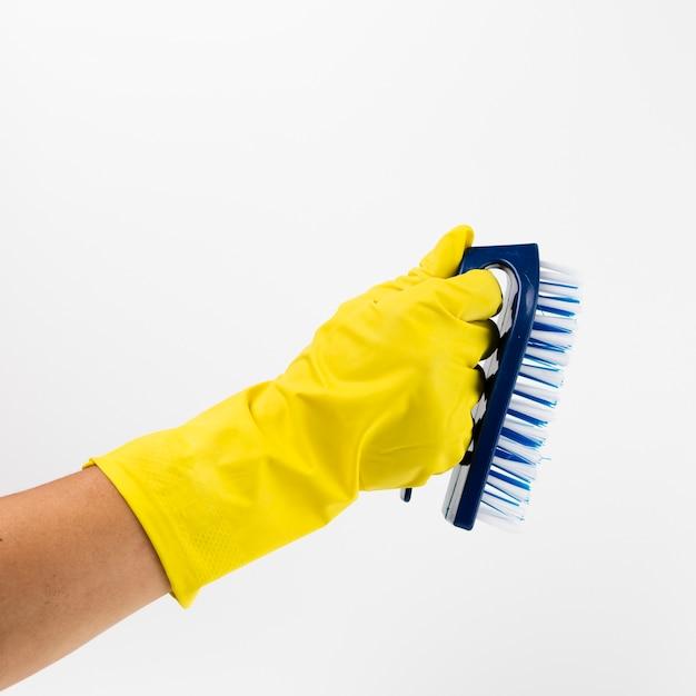 黄色の手袋とブラシでクローズアップ手 無料写真