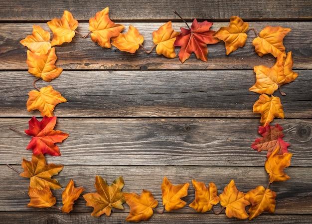 木製テーブルの上のカラフルな葉を持つビューフレームの上 無料写真