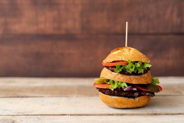 木製の背景を持つ正面ハンバーガー 無料写真