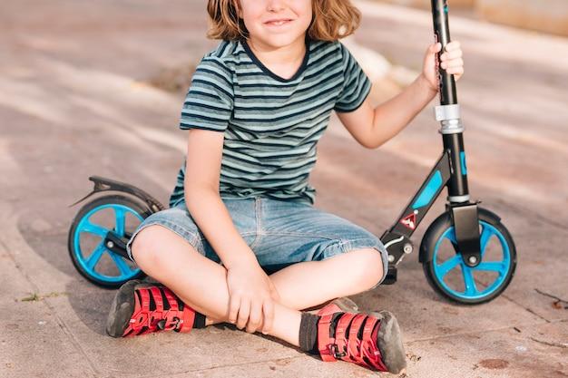 スクーターで公園に座っている少年 無料写真