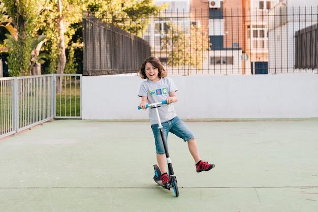 スクーターで少年のロングショット 無料写真