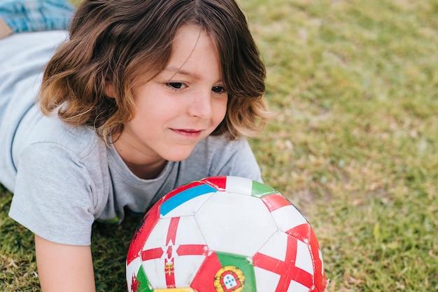 Вид спереди ребенка, играющего в траве Бесплатные Фотографии