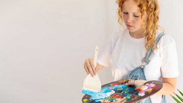Вид сбоку девушка с предметами живописи Бесплатные Фотографии