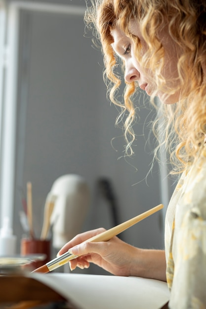 Крупным планом творческая женщина, живопись на дому Бесплатные Фотографии