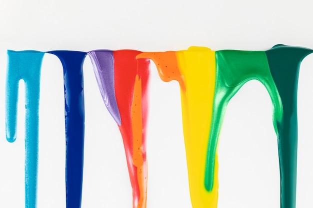 Разноцветные краски капают на белом фоне Бесплатные Фотографии